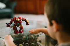 Red and Yellow Iron Man Toy on Glass Table Near Baby Royalty Free Stock Photography
