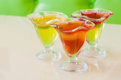 Red yellow jelly in glass plate, citrus fruit gelatin dessert beige green background Stock Photo