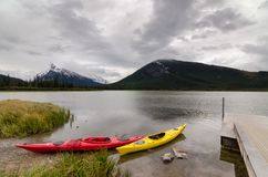Red and yellow kayaks sitting by a dock with a view of Mount Rundle royalty free stock image