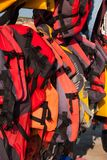 Red and yellow life jackets. Many life belts hanging on the beach royalty free stock photography
