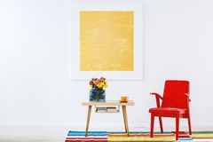 Red and yellow living room. Red armchair next to a wooden table with flowers on colorful carpet in living room interior with yellow painting royalty free stock photography