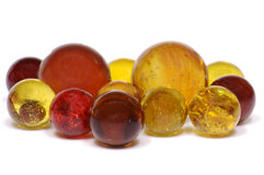 Red & Yellow Marbles. A group of Fall colored red, orange, yellow, and brown glass marbles isolated on a white background Royalty Free Stock Images