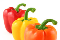 Red yellow orange. Close up of red yellow and orange bell peppers isolated on white Royalty Free Stock Photo