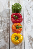 Red yellow orange green bell peppers on wooden table, high angle view Royalty Free Stock Photo