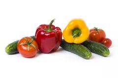 Red yellow and orange peppers with tomatoes on a white background. Cucumbers with colorful peppers in composition on a white backg. Round royalty free stock photography