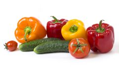 Red yellow and orange peppers with tomatoes on a white background. Cucumbers with colorful peppers in composition on a white backg. Round stock photography
