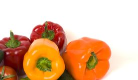 Red yellow and orange peppers with tomatoes on a white background. Cucumbers with colorful peppers in composition on a white backg. Round stock image