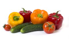 Red yellow and orange peppers with tomatoes on a white background. Cucumbers with colorful peppers in composition on a white backg. Round royalty free stock images