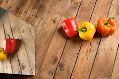Red Yellow Orange Peppers on wood stock photo