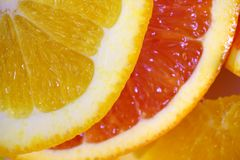 Red and yellow orange slices. Quite close up photo of bright red and yellow orange slices on some pure white surface. Citrus are one of the most popular food Stock Photos