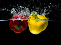 Red and Yellow Paprika Splash in Water Isolated on black Background Royalty Free Stock Photography