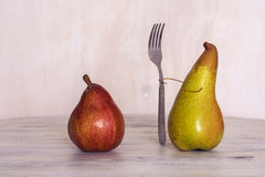 Red and yellow pear on the table. Pear with a fork. Still life with pears. Royalty Free Stock Image