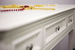 Red and yellow pearls necklace on vintage table. Stock Photos