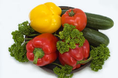 Red and yellow pepper. Red and yellow pepper with greens in a basket on a white background Stock Photo