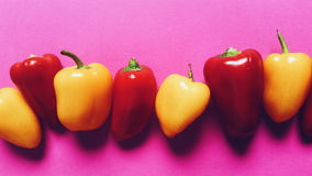 Red and yellow pepper. On a pink background, the top view Royalty Free Stock Photography