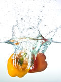 Red and yellow pepper splashed into water Royalty Free Stock Photo