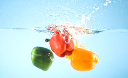 Red and yellow pepper splashed into water Royalty Free Stock Image