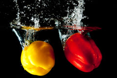 Red and Yellow Pepper Water Splash. Red and yellow pepper drop in a water tank creating a splash Royalty Free Stock Photography