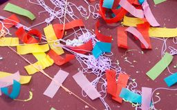 Multi-colored streamers and string on a maroon background. Red, yellow, pink, green, and blue streamers, confetti, and string on a maroon background stock image