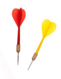 Red and yellow plastic darts on white background. Stock Photos