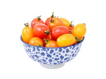 Red and yellow plum tomatoes in a blue and white china bowl Stock Images