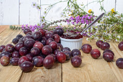 Red and yellow plums on a wooden table Royalty Free Stock Photos