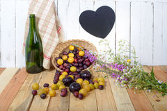 Red and yellow plums on a wooden table with slate Stock Photo