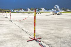 Red and yellow pole sign with a chain prohibits people of passing on an airport stock image