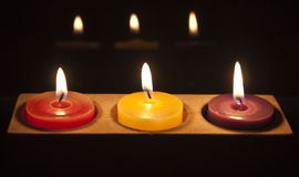 Red, yellow and purple candles in a row. A row of candles growing in the dark Royalty Free Stock Images