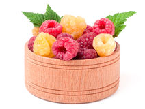 Red and yellow raspberries in wooden bowl isolated on white. Red and yellow raspberries in a wooden bowl isolated on white background Royalty Free Stock Photography