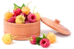 Red and yellow raspberries in wooden bowl isolated on white Stock Photo