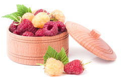 Red and yellow raspberries in wooden bowl isolated on white Royalty Free Stock Images