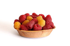 Red and yellow raspberries in the wooden platen isolated on whit Stock Images