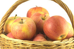 Red and yellow ripe apples in brown wicker basket isolated Royalty Free Stock Photography