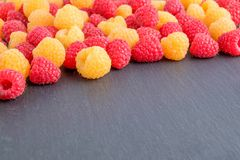 Red and yellow ripe natural fresh raspberries on black stone. Background. Close-up view. Copy space for text Stock Photo
