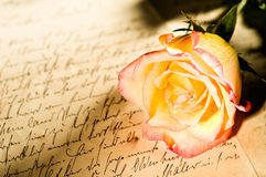 Red yellow rose over a hand written letter Stock Image