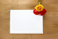 Red and yellow roses on wooden background. Blank sheet of paper Royalty Free Stock Image