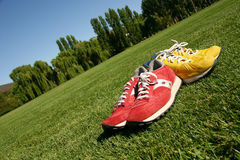 Red and yellow running shoes on a sports field. With a deep blue sky Royalty Free Stock Photography