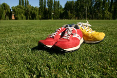 Red and yellow running shoes on a sports field. With a deep blue sky Stock Images
