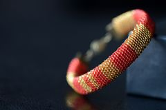 Red and yellow shiny bracelet made of small seed beads. Close up Royalty Free Stock Image