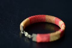 Red and yellow shiny bracelet made of small seed beads. Close up Royalty Free Stock Photo