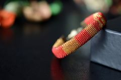 Red and yellow shiny bracelet made of small seed beads. Close up Royalty Free Stock Images