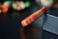 Red and yellow shiny bracelet made of small seed beads. Close up Royalty Free Stock Photos