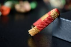 Red and yellow shiny bracelet made of small seed beads. Close up Stock Images