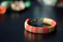 Red and yellow shiny bracelet made of small seed beads. Close up Stock Photography
