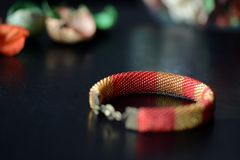 Red and yellow shiny bracelet made of small seed beads. Close up Stock Photo