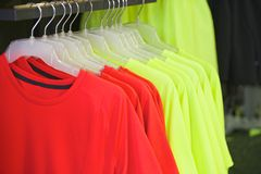 Red and yellow shirts on hangers fashion boutique Royalty Free Stock Images