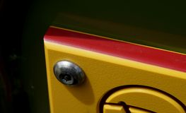 Red and Yellow Sign. Detail of part of a yellow with red rimmed sign mounted with stainless steel hardware Stock Photos