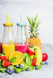 Red and yellow smoothies drinks in bottles with fruits ingredients on light background. Healthy lifestyle. Detox or diet food concept stock image
