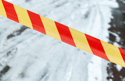 Red and yellow striped tape on winter road Royalty Free Stock Image